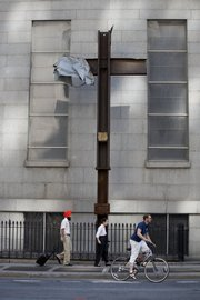 People pass a steel cross, a remnant of the attacks on the World Trade Center, now being stored at a church close to the infamous site. As the nation prepares for the seventh anniversary of Sept. 11, 2001, many have mixed feelings about the day that changed U.S. history yet grows more remote with each passing year.