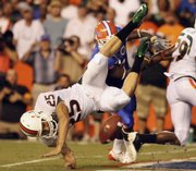 Miami punter Matt Bosher is upended after getting his punt blocked in the second quarter. The Hurricanes took a safety on the play. Florida defeated Miami, 26-3, on Saturday in Gainesville, Fla. Story on page 7C.