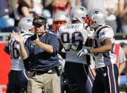 Coach Bill Belichick, left, claps after the Patriots defense stopped Kansas City from scoring with less than a minute left in the fourth quarter.
