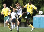 Nick Krug/Journal-World Photo.Free State junior Sam Passig pushes the ball upfield between Shawnee Mission South sophomore Doug Brown, left, and junior Michel Afrifa during the first half Tuesday, Sept. 9, 2008 at Free State High School.