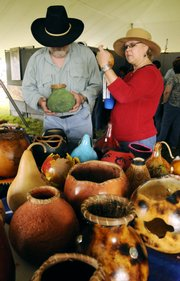 James Hopper, left, and his wife, Marilou Cavin, inspect decorative gourds by artist Marty McKinney of Columbia, S.C., at the Haskell Indian Art Market.