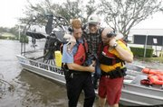 Jim Wathens, 84, center, is helped from a rescue boat Saturday in Galveston, Texas, by police officer Bobby Sanderson, left, and beach patrol's Shean Migues after Hurricane Ike hit the Texas coast. Hundreds of people in Texas and Louisiana were awaiting rescue from high water.