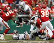 Oakland Raiders running back Justin Fargas (25) leaps over teammate Robert Gallery and through Kansas City Chiefs linebacker Derrick Johnson, left, and DaJuan Morgan. The Raiders routed the Chiefs, 23-8, on Sunday in Kansas City, Mo.