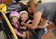 The Nichols family got a bicycle trailer about a year ago and now use it to take family rides together. Loading up for a ride, from left, are Tess Nichols, 3, her sister, Maeve, 18 months, and their mother, Eliza Nichols.