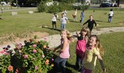 From left, Perry Elementary School third-graders Hannah Waugh, Katie Gleason and Shelby Hetherington watch as a monarch butterfly passes overhead in the new Children's Learning Garden.