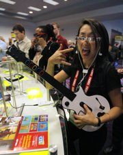 Judy Mellett of Toronto poses while playing a video game through Myvu's personal media viewer at the Consumer Electronics Show in Las Vegas in this Jan. 9 file photo.