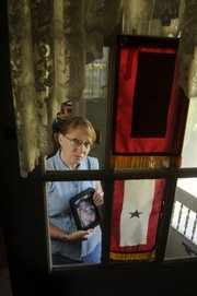 Candy Wasser, Ottawa, holds a picture of her oldest son, Chris, shown from his senior year in high school. Chris wanted to be a Marine, and when he turned 18, he enlisted. Three Marines and a chaplain informed the Wassers of their son's death at 11:30 p.m. April 8, 2004. Two flags hang on the front door - one signifies a son in service; the other signifies a soldier killed in action.