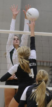 Free State senior Melissa Burch, left, goes up for a block against Blue Valley Northwest junior Taylor Henning in the Firebirds' first match against the Huskies Thursday at Free State High School.