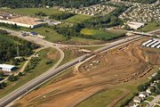 This aerial photograph looks southwest across the construction site for upgrades to the West Lawrence interchange, which is exit 202 on the Kansas Turnpike. At the right side of the photo - which is the north end of the site, across a new bridge being built - is the circular foundation for what will be a new roundabout, one designed to handle traffic exiting the turnpike from the east and getting onto the turnpike to go west.