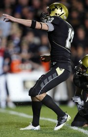 Colorado kicker Aric Goodman, left, reacts after connecting on the winning field goal in the Buffaloes' 17-14 overtime victory over West Virginia. CU won Thursday in Boulder, Colo.