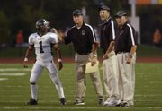 Free State High School coaches send the next play in with junior Camren Torneden (1) on Friday, Sept. 19, 2008 during the Firebirds' game against Shawnee Mission Northwest at the Shawnee Mission North campus.