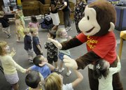 Curious George greets children on their way to storytime Tuesday at the Lawrence Public Library at 707 Vt. The famous children's book character was on hand at the library to promote this Saturday's River City Reading Festival.