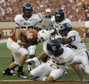 Texas quarterback Colt McCoy (12) escapes a handful of Rice defenders as he scrambles over his right end for an eight-yard touchdown Saturday in Austin, Texas. McCoy later passed Major Applewhite for the Texas all-time record in touchdown passes with 62.