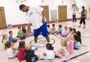Kansas University basketball player Marcus Morris reaches down to slap hands with some of the kindergartners gathered at Hillcrest School, 1045 Hilltop Drive. Marcus, his twin brother Markieff Morris and fellow player Tyrel Reed talked about nutrition and exercise, played a game of dodgeball and signed autographs Wednesday at the school.