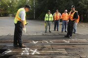 Wayne Harbourn, resident manager of field safety for BNSF, shows law enforcement personnel a simulated accident on the tracks in east Lawrence, as local and state law enforcement agencies worked with officials from Burlington Northern Santa Fe Railway on Wednesday.
