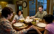 "The Wade family, from left, Susan, Angelica, 13, John and, Andrea, 11, gather around the table for prayer in their Lawrence home. The family has been singing ""Thank You Father"" as their grace since the girls were very young."