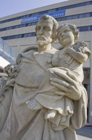 A statue of St. Joseph holding the infant Jesus stands outside of Creighton Medical Center in Omaha, Neb., where nine siblings were abandoned by their father Wednesday. Eleven children ranging in age from 1 to 17 were left at hospitals Wednesday under Nebraska's unique safe haven law, which allows caregivers to abandon not only infants but also teenagers without fear of prosecution.