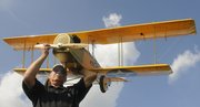 Bill Elkins works Wednesday on his 20-to-1 model of a WW1 Curtiss Jenny. Elkins' plane and many other Giant Scale R/C airplanes will be putting on a show this weekend below Clinton Dam, at the Jayhawk Model Masters Field. The event starts Saturday at 9 a.m.
