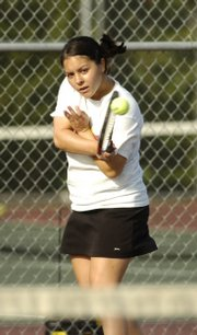 Lawrence High junior Jordan Payne hits a return during her doubles match. Payne was a double winner Monday in the Lions&#39; victory over Free State at the Lawrence Tennis Center.