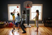 Betsy Six, center, and children Henry, 6, Sam, 8, and Emily, 10, play basketball at their Lawrence home. Six volunteers at Hillcrest School, where three of her children attend, and also is an instructor at Kansas University's School of Law.