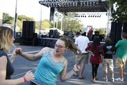 Carolina Poudfoot, center, dances with her sister, Sierra Farwell, both of Lawrence, on Friday during the third annual Get Downtown music festival in the 800 block of New Hampshire Street. The festival continues today.