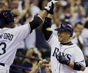 Tampa Bay's Akinori Iwamura, right, accepts congratulations from Carl Crawford after hitting a two-run home run. The Rays defeated the Chicago White Sox, 6-2, on Friday in St. Petersburg, Fla., to take a 2-0 lead in their series.