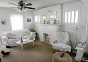 Walls and furniture painted white brighten the living room of Patty Kerr's Firestone Park bungalow in Akron, Ohio. Kerr's home is the embodiment of frugal fashion.