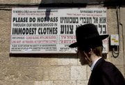 An ultra-Orthodox man walks past a sign calling on women to dress modestly Sept. 12 in a religious neighborhood in Jerusalem. In Israel's ultra-Orthodox Jewish community, where the rule of law takes a back seat to the rule of God, religious zealots are on a crusade to stamp out unchaste behavior.
