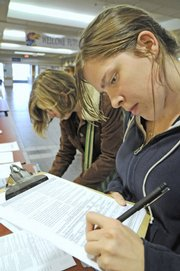 Shannon Craft, left, a Kansas University sophomore from Lawrence, and Kara Hudson, a junior from Wichita, register to vote on Tuesday at the Kansas Union. Voter registration has soared in Douglas County as the Nov. 4 general election approaches.