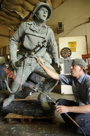 "Alan Austin applies a patina to the bronze sculpture ""Medic"" at Ad Astra Art Bronze. The sculpture, depicting a soldier flanked by a medic, is the most recent in a series of bronze sculptures by local artist Jim Brothers. It will be placed at the National D-Day Memorial in Bedford, Va. The sculpture will be on display from 1 p.m. to 5 p.m. Sunday at the Union Pacific Depot in Lawrence before making its way to the D-Day Memorial for a Veterans Day unveiling ceremony Nov. 11."