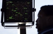 Air traffic controller Karl Haynes Jr. stands beneath a radar screen Sept. 18 in the control tower at Washington's Reagan National Airport. A satellite-driven network, dubbed NextGen, would save fuel by ditching World War II-era radar technology and enabling GPS-equipped planes to fly the shortest route between two points: a straight line.