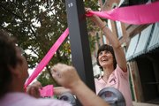 Jane Landau, right, and Jan Ackerly, both of Lawrence, tie a pink ribbon to a pole on Massachusetts Street on Sunday, Oct. 12, 2008 in an effort to raise breast cancer awareness. October is Breast Cancer Awareness Month. On Oct. 25, LMH will host the 16th Annual Stepping Out Against Breast Cancer Dance as a fundraiser to benefit women who need to get mammograms.