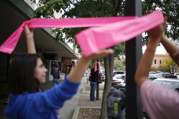 Tori Hawk, 16, left, and her mother, Lori Nation, right, attach a ribbon to a pole along Massachusetts Street on Sunday, Oct. 12, 2008, to help raise breast cancer awareness. In the background Meri Smith fastens a ribbon to another pole.