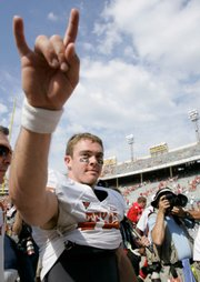 Texas quarterback Colt McCoy, in photo at left, celebrates after the Longhorns' 45-35 victory over OU Saturday in Dallas.