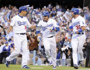 Los Angeles Dodgers Hiroki Kuroda, left, and Casey Blake, right, celebrate with Russell Martin after Martin and Blake scored on a three-run RBI triple by Blake DeWitt. The Dodgers defeated the Phillies, 7-2, on Sunday in Los Angeles to cut Philadelphia's lead in the NLCS to 2-1.