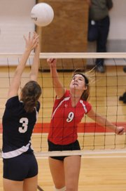 Lawrence High sophomore Mary Coldsnow lifts a shot over Manhattan High junior defender Shelbi Doehling during the first match of their home volleyball quad Tuesday, Oct. 14, 2008 at LHS.
