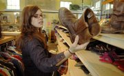 Katy Wade, 25, of Lawrence, looks through some boots at the Social Service League Thrift Store, 905 R.I. Secondhand stores and pawn shops are seeing an increase in goods coming in, but sales are sluggish.