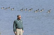 Jerry Schecher, general manager at Clinton State Park, eyes a fall flock of Canada geese at the lake. Schecher says hard work early in his life helped him attain his career goals.