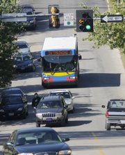 A KU bus, part of the KU on Wheels transit system, runs a route into downtown Lawrence for driver training. Lawrence has talked about signing a letter of intent with KU regarding the organization's two bus systems. The merger could bring better coordination of routes and use of the two bus systems.