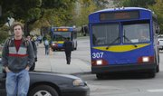 A KU on Wheels Bus departs a campus bus stop in front of the Kansas Union on Oct. 15. City commissioners have unanimously agreed to approve a letter of intent that sets a goal of coordinating, consolidating or merging the city and university bus systems by July.