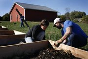 Amber Lehrman, center, and Chad Harper, right, both of Lawrence, construct compost containers Sunday at Faith Church of Nazarene, 1020 Kasold Drive. The church, with the help of the Lawrence Sustainability Network and volunteers, is building a community garden.