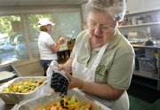 Lawrence resident Dianna Keller works to prepare a fresh fruit salad for a lunch order alongside Norma Simmons at her catering kitchen. She made the jump from daycare provider to caterer in the last year and serves 130 to 170 meals each week.