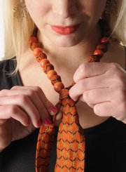 Wear a fun necktie as jewelry. Beads and embellishments add femininity.