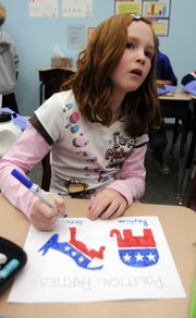 Macie Reeb, a fourth-grader at Langston Hughes School, colors the symbols for the Democratic and Republican parties. Macie and her classmates were learning all about political parties on Tuesday.