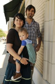 Amanda Berger carries her son, Jonah, 17 months old, using a baby sling, as her husband, Jesse Gray, walks nearby along Massachusetts Street.