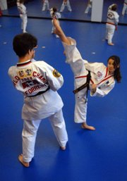 Dru Forrester, 48, and her daughter Sarah Jacobson, 13, practice kicks during their tae kwon do practice.