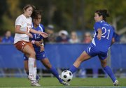 KU's Emily Cressy (21) takes the ball from Texas' Alisha Ortiz as KU's Lauren Jackson watches on.