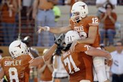Texas&#39; Colt McCoy (12) is lifted by teammate Trent Perkins (71) as he celebrates with Jordan Shipley (8). Texas held off Oklahoma State, 28-24, on Saturday in Austin, Texas.