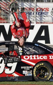 Carl Edwards does a back flip after winning the Pep Boys Auto 500 NASCAR Sprint Cup Series race. Edwards edged Jimmie Johnson on Sunday at the Atlanta Motor Speedway in Hampton, Ga.