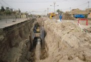 Iraqi men work last week on a planned sewage treatment system that is three years overdue in Fallujah, 40 miles west of Baghdad, Iraq. A new report shows the U.S. project has been troubled by violence, staggering waste, endless delay and U.S. and Iraqi incompetence.